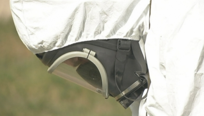 Mannen in witte pakken doen meetoefeningen aan SCK