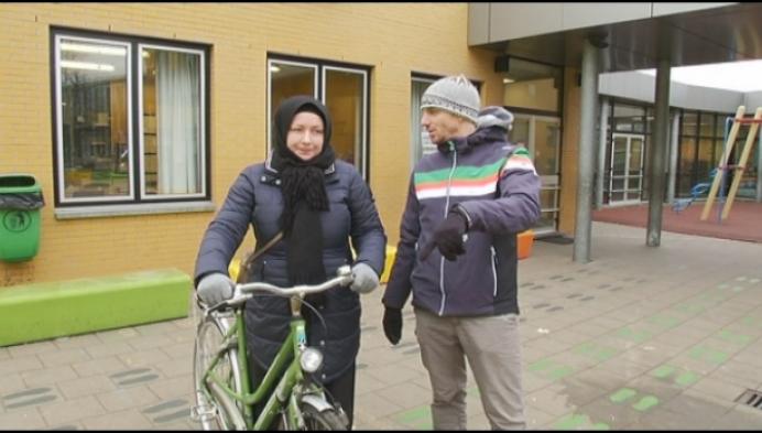 Moeders van leerlingen leren fietsen in basisschool