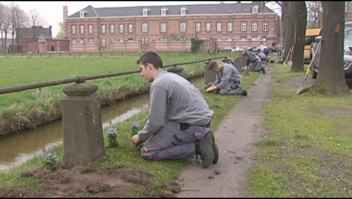 Jongeren planten vergeet-mij-nietjes aan de gevangenispoort van Hoogstraten