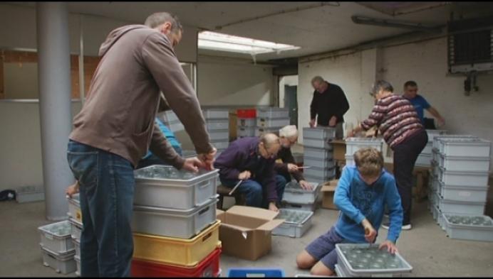 Vrijwilligers poetsen bokalen voor kaarsjes in het Begijnhof