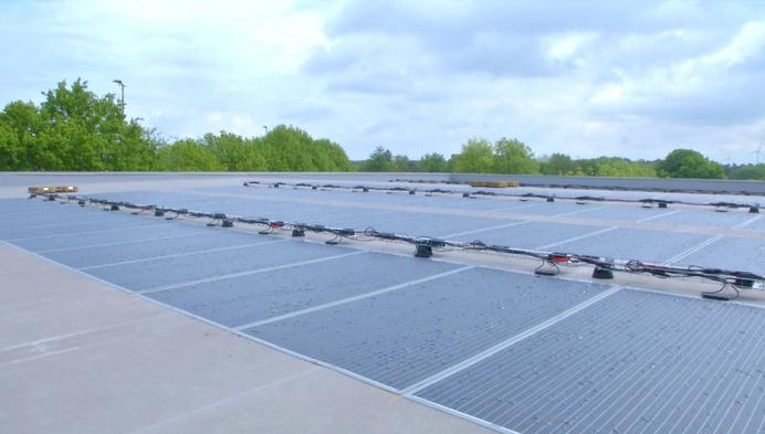 Gekleefde(!) zonnepalen op dak van sporthal